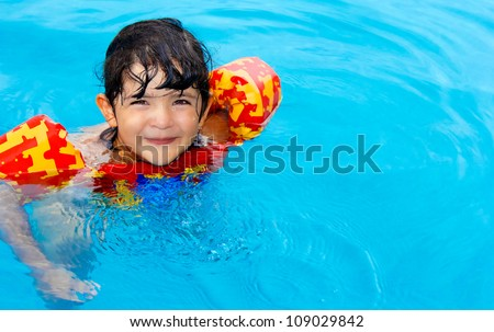 Cute little girl with hazel eyes and enjoy her time in the swimming pool - stock photo