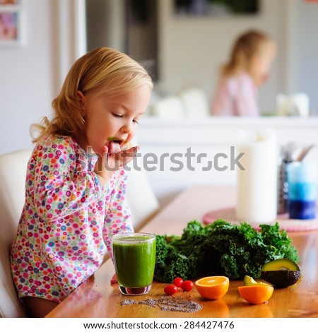Cute little girl with healthy fruit and vegetables and a green smoothie juice inside the house