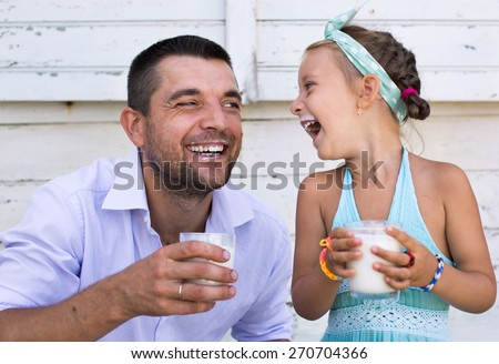 Cute little girl with her father holding glasses of milk over wooden background - stock photo