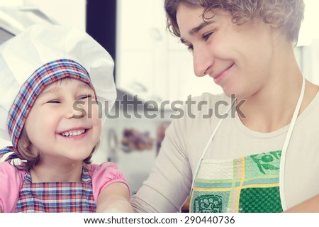 Cute little girl with her mother bake cookies at home kitchen - stock photo