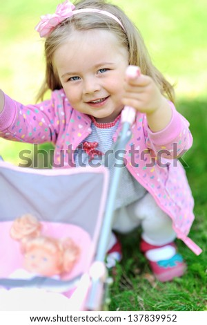 Cute little girl with her toy carriage - closeup portrait - stock photo