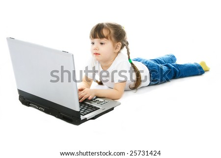 cute little girl with lies on the floor with a laptop