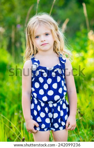 Cute little girl with long blond curly hair, outdoor full length portrait in summer park on bright sunny day. Pensive child in green grass field. Calmness and tenderness. - stock photo