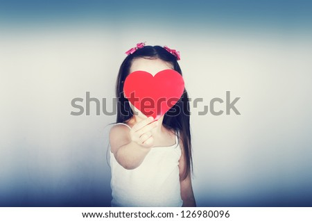 Cute little girl with long hair playing with a red heart - stock photo