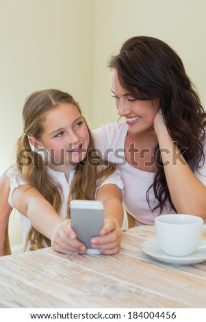 Cute little girl with mother photographing through mobile phone at table in house - stock photo