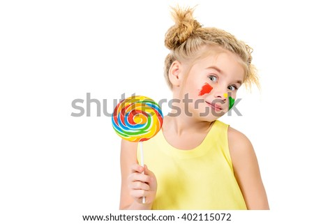 Cute little girl with painted colorful cheeks licking a lollipop. Happy childhood. Isolated over white. - stock photo