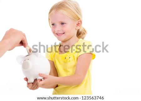 cute little girl with piggybank receiving money - stock photo