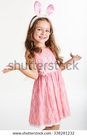 Cute little girl with pink bunny ears isolated on white background in studio - stock photo