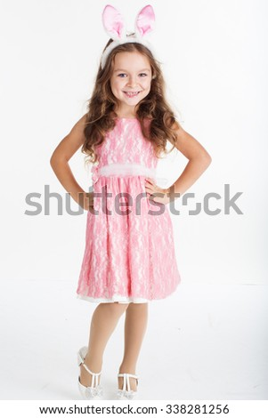 Cute little girl with pink ears bunny on white background. - stock photo