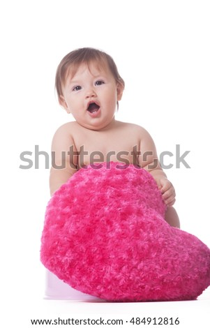 Cute little girl with plushy pink heart on isolated white