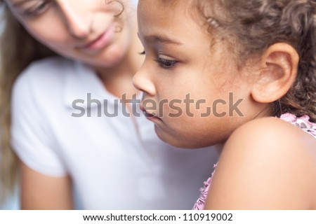 Cute little girl with sad look looking at something with her mother behind - stock photo