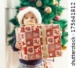 Cute little girl with Santa hat holding a Christmas gift at home. - stock photo