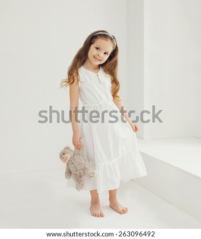 Cute little girl with teddy bear at home in white room - stock photo