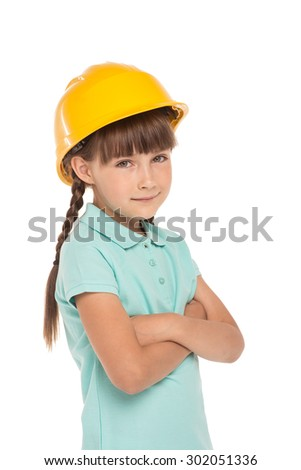 Cute little girl with two braids is isolated on white background. Girl looking at camera and wearing yellow helmet