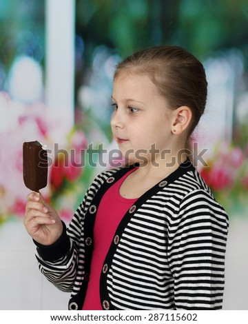 Cute little girl wonderingly stares at ice cream in her hand - stock photo