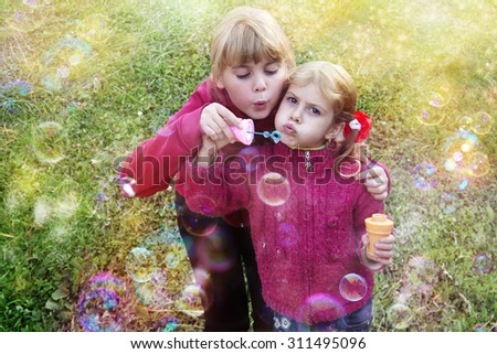 Cute little girls are blowing a soap bubbles. Children playing on the grass, happy carefree childhood. Toned/filtered photo with warm summer lighting.  - stock photo