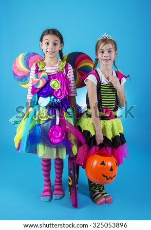 Cute little girls in Halloween costumes ready to go trick or treating - stock photo