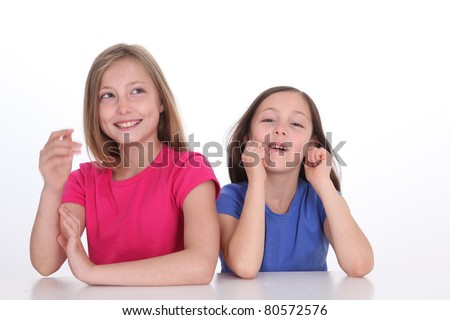 Cute little girls laughing on white background - stock photo