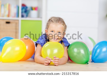Cute little girls lying on the floor with colorful balloons - stock photo