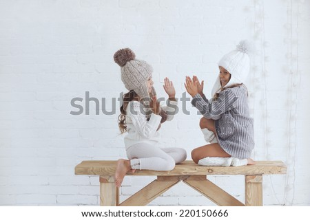 Cute little girls of 5 years old wearing same knitted trendy winter clothes posing over white brick wall - stock photo