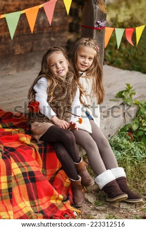 Cute little girls posing over wooden house background. Autumn concept. - stock photo