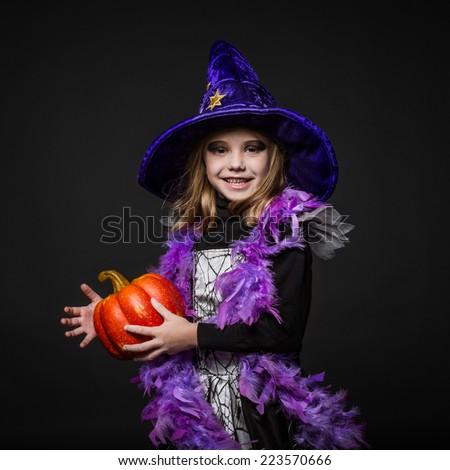 Cute little Halloween witch holding a orange pumpkin. Studio portrait over black background  - stock photo