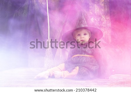 cute little halloween witch with cauldron and smoke - stock photo