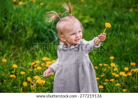 Cute little happy girl laughs and rejoices, looking for someone or something and gives dandelion on the meadow with dandelions and green grass - stock photo