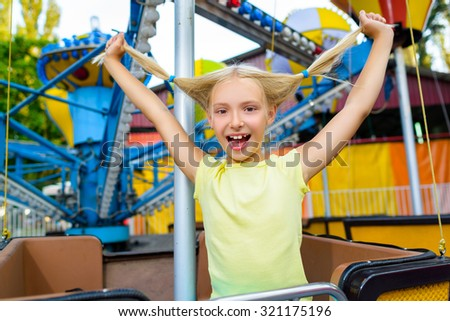Cute little happy smiling girl riding a Carnival Carousel at summer theme park - stock photo