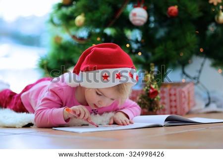 Cute little kid writes letter to santa adorable toddler girl in santa