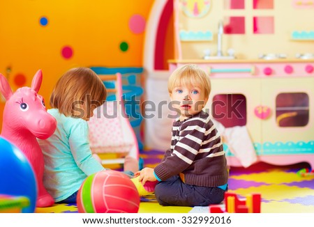 cute little kids playing together in daycare center - stock photo