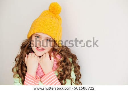 Cute little lady wearing yellow woolen cap and warm scarf against white background