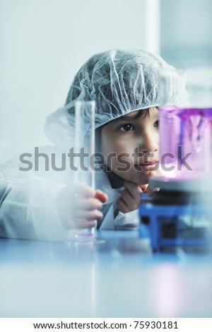 cute little male child have experiment with test tubes in bright modern lab - stock photo
