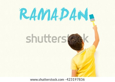 Cute little Muslim kid drawing Ramadan with painting brush on wall background - stock photo