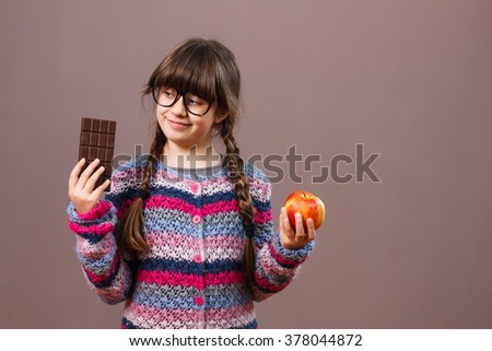 Cute little nerdy girl is holding apple and chocolate in her hands,she likes  chocolate more than apple.I would rather eat chocolate ! - stock photo