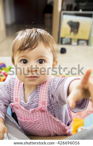 Cute little one year old kid with wide open eyes looking at camera and pointing at it