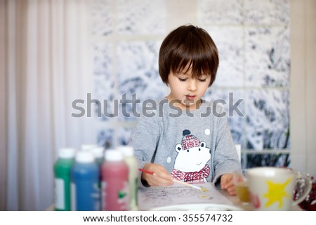 Cute little preschool boy, drawing picture at home, wintertime - stock photo