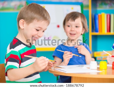Cute little preschool children drawing with colorful paints at kindergarten - stock photo