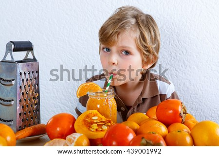 Cute little preschool kid boy drinking fresh healthy organic smoothie. Healthy meal and drink. Orange fruits and vegetables. - stock photo