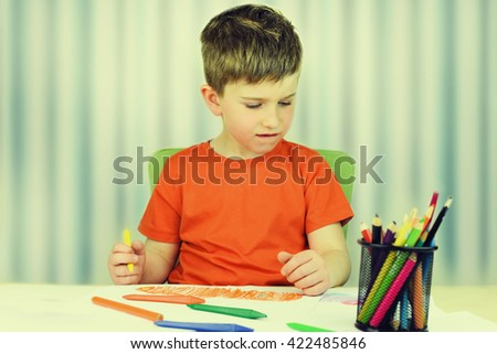 Cute little preschooler child drawing at home.