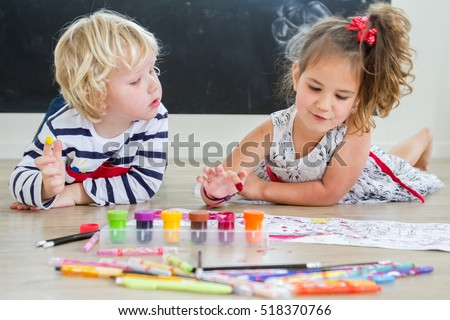 Cute little preschooler children - boy and girl - drawing at home
