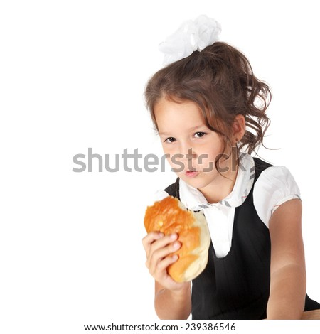 cute little preschooler girl eating a bun - stock photo