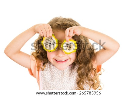 Cute little preschooler girl holding pitahaya slices in front of her eyes isolated on white - stock photo