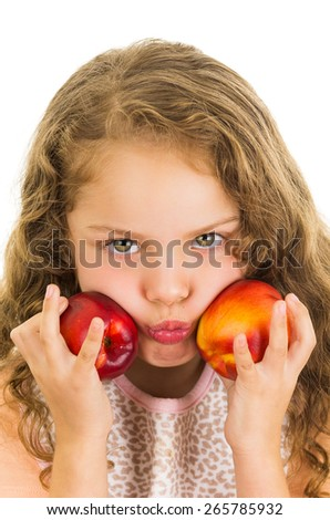 Cute little preschooler girl holding two peaches in front of her cheeks isolated on white - stock photo