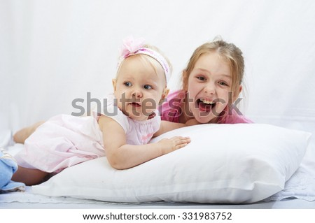 cute little preteen sister play with newborn  baby girl on a white pilllow with background - stock photo