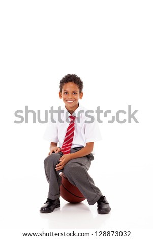 cute little primary schoolboy sitting on basket ball on white