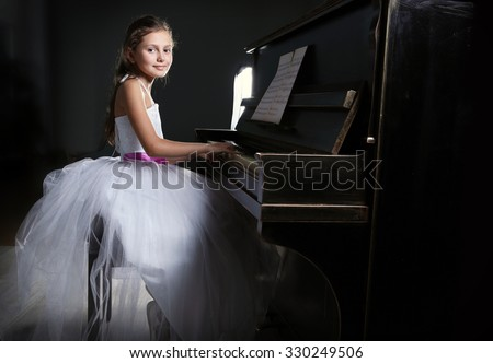 Cute little princess girl plays piano in the dark room - stock photo
