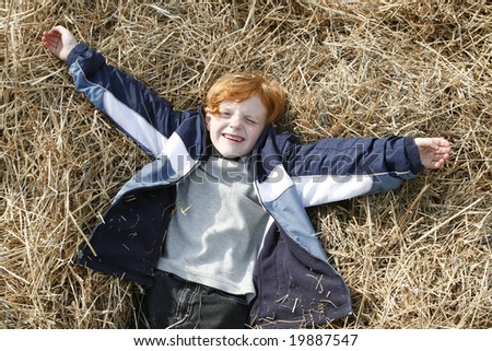 Cute little Red haired boy playing in the Hay.