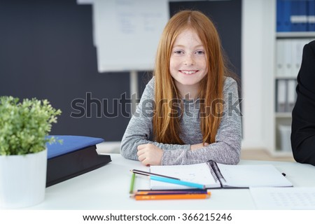 Cute little redhead girl with a lovely engaging smile sitting at a desk in an office doing her homework - stock photo