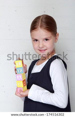 "Cute little schoolgirl in school uniform holding the word ""learn"" from the children's blocks on Education - stock photo"